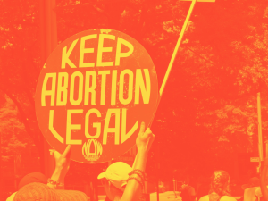 "A pair of arms holding up a retro ""keep abortion legal NOW"" sign against some trees, the photo edited into a orange and yellow combination"