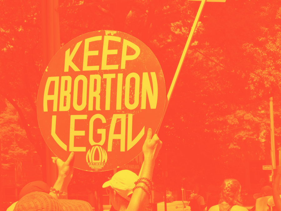"""A pair of arms holding up a retro """"keep abortion legal NOW"""" sign against some trees, the photo edited into a orange and yellow combination"""