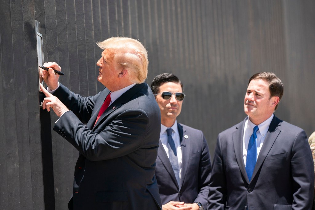 President Donald Trump signs a plaque on the U.S. border for the 200th mile of new border wall along the U.S.-Mexico border near Yuma, Ariz.
