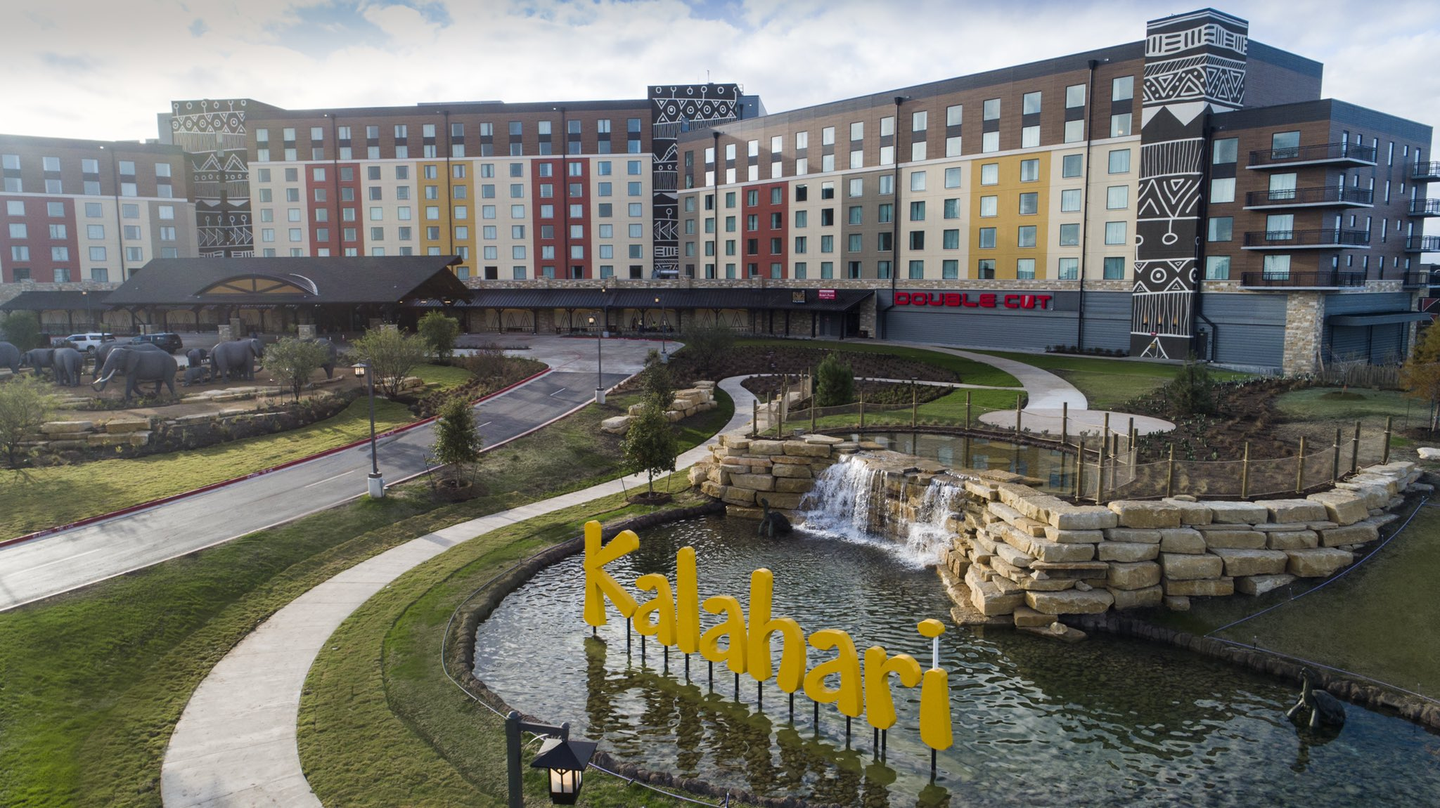 A digital rendering of the outside of the Kalahari Round Rock location, with a yellow sign and stripe-pattern painted buildings and statues of elephants