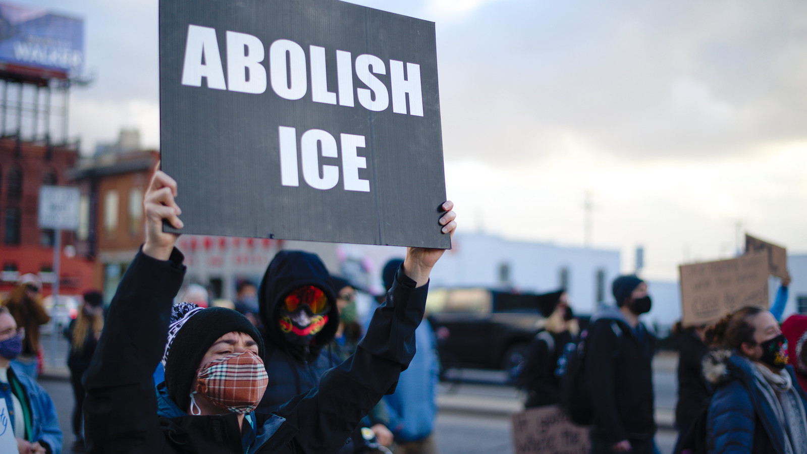 """A protester with a face mask at an October 2020 demonstration in Minneapolis holding a black sign that says """"Abolish ICE"""" in white block letters"""