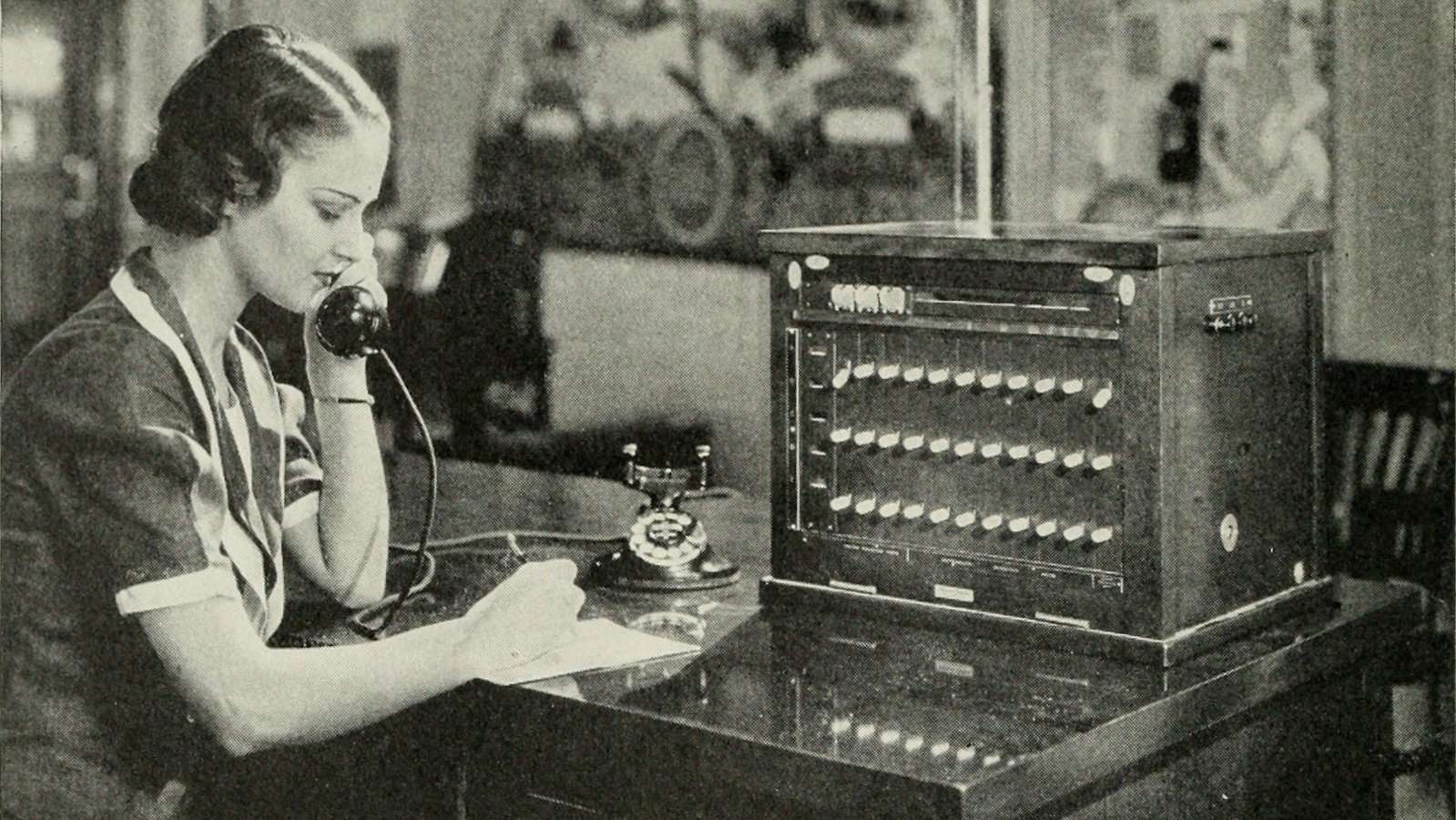"""Image from page 287 of """"Bell telephone magazine"""" (1922) of a woman operating a local switchboard"""