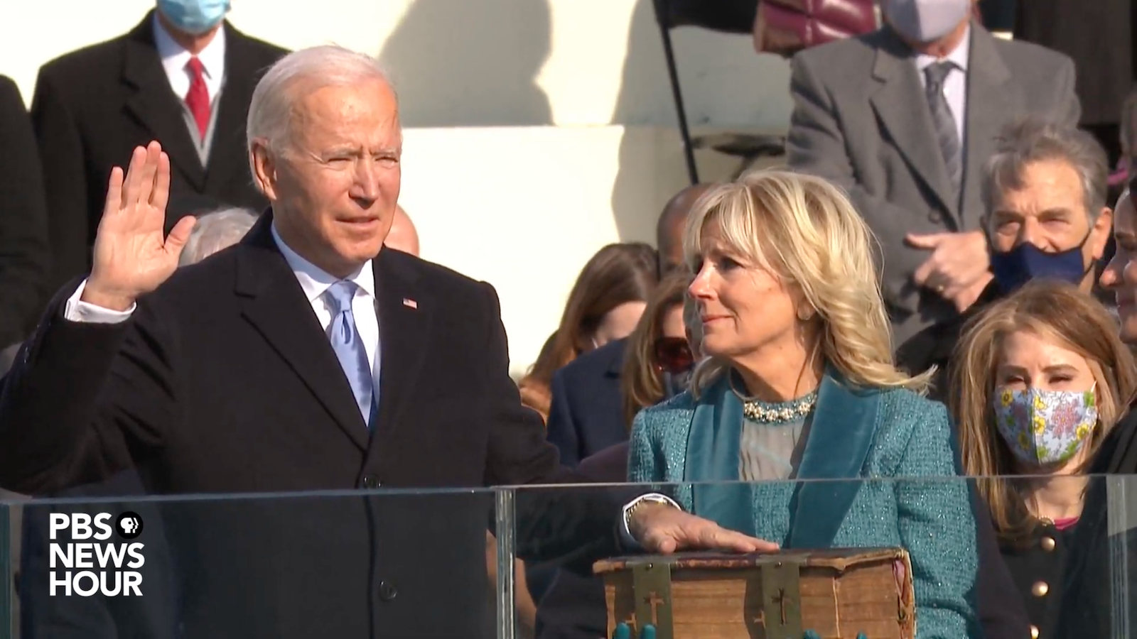Joe Biden with his hand on a bible held by Jill Biden, swearing in to be the 46th president of the United States.