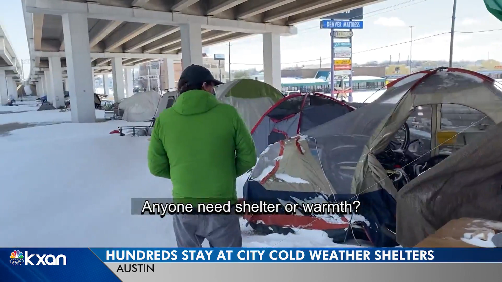 Billy Tweedie, a priest, walks through a group of tents surrounded by snow under an overpass in Austin to see if anyone is left staying out in the cold.