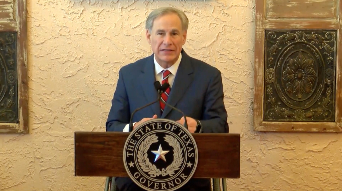 Greg Abbott sitting in front of a crowd of people after announcing he was reopening the state