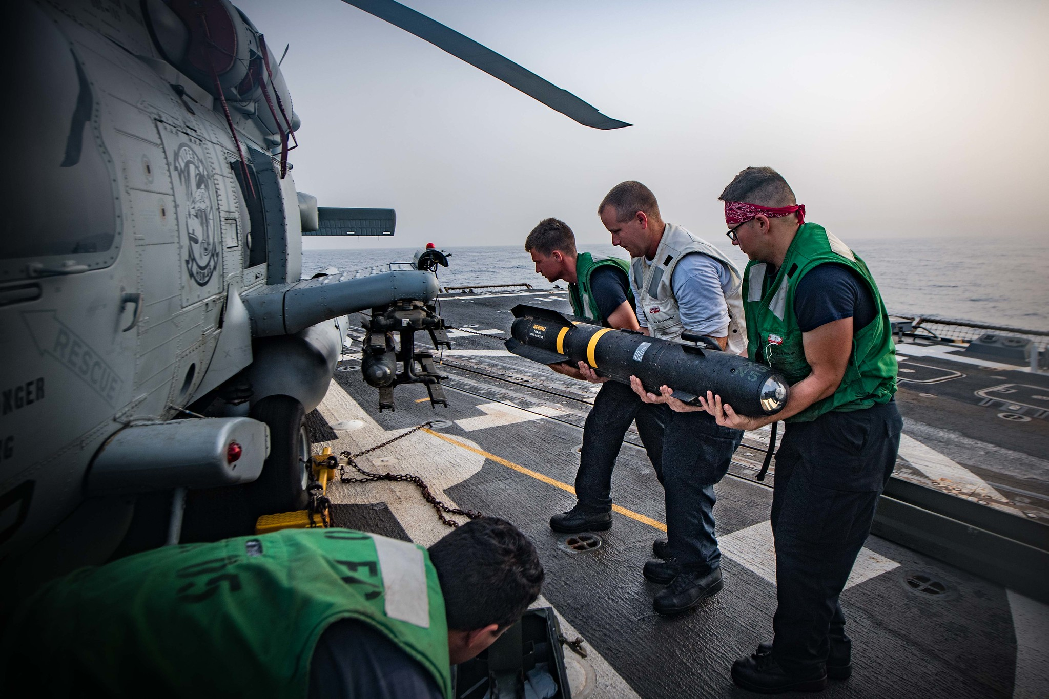 U.S. Navy Sailors load an AGM-114 Hellfire missile onto an MH-60R Sea Hawk helicopter.