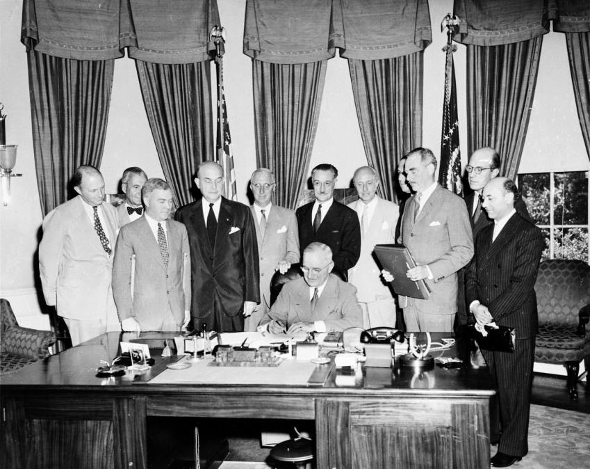 US President Harry S. Truman signing the North Atlantic Treaty in the Oval Office, surrounded by several foreign dignitaries, on August 24, 1949
