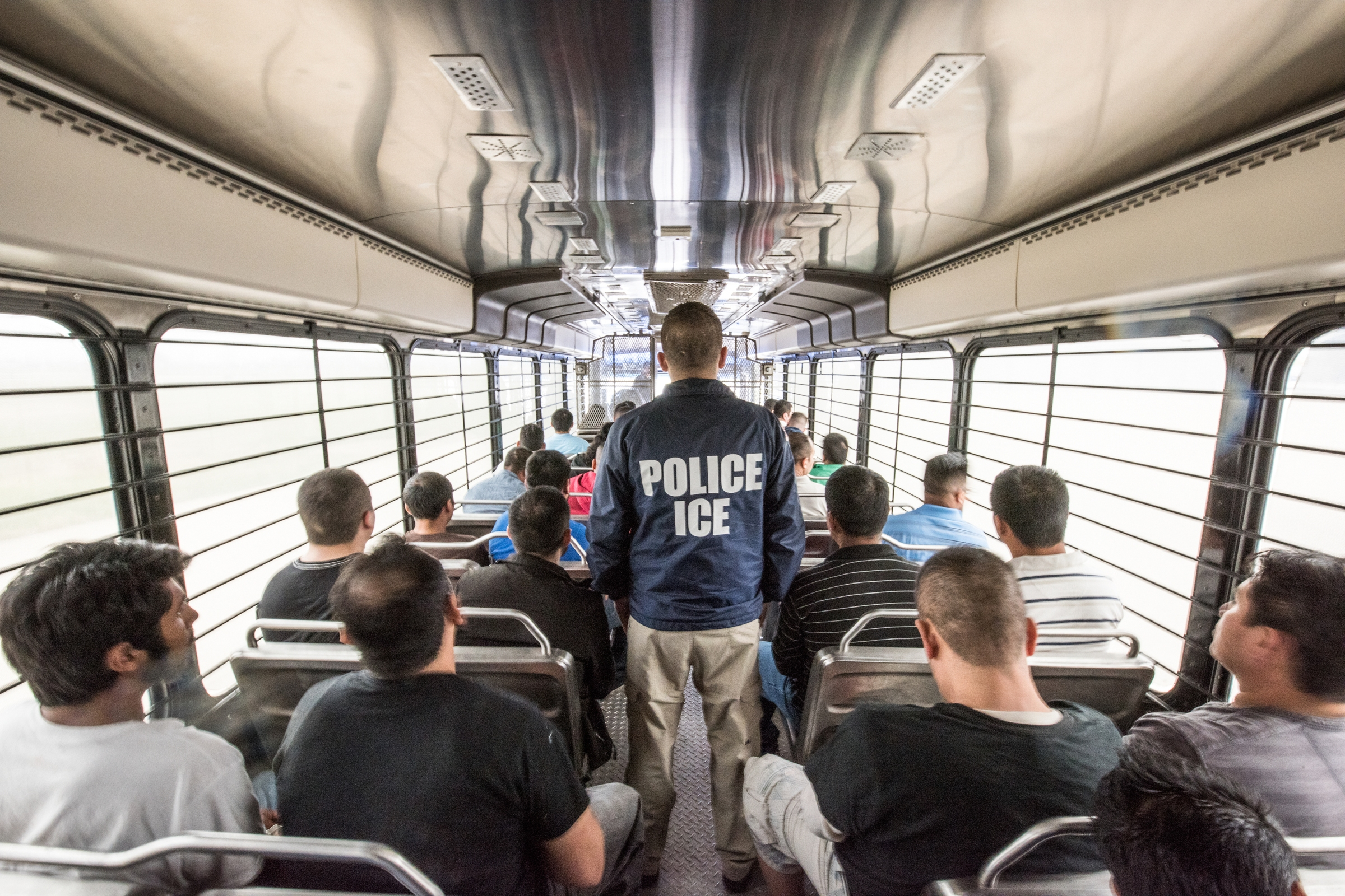 An ERO officer riding with people in custody to an ICE detention facility