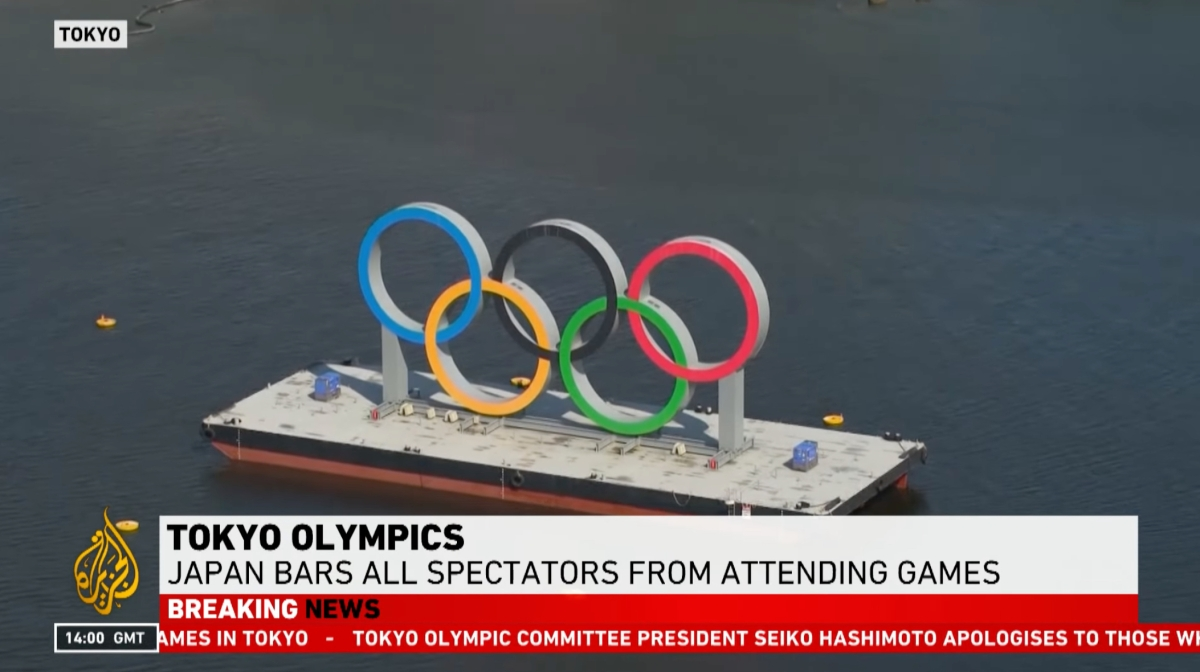 The Olympic rings are shown in a news story about Japan banning spectators from attending games in Tokyo.
